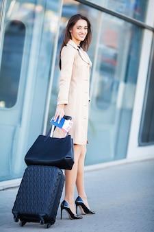 Urlaub. lächelnde passagierin, die das tor verlässt und den koffer durch die flughafenhalle zieht