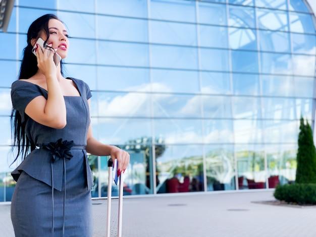 Urlaub. lächelnder weiblicher passagier, der fortfährt, das tor zu verlassen, das koffer durch flughafenhalle zieht