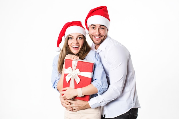 Urlaub. porträt des attraktiven jungen paares in den weihnachtsmützen mit geschenk