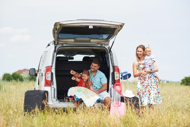 Urlaub, reisen - glückliche familie bereit für die reise für die sommerferien. die leute haben spaß und fotografieren am telefon. machen sie ein selfie zur erinnerung an die reise
