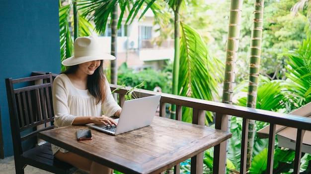 Urlaub reisende laptop-technologie-konzept-frau, die an ihrem laptop im urlaub arbeitet