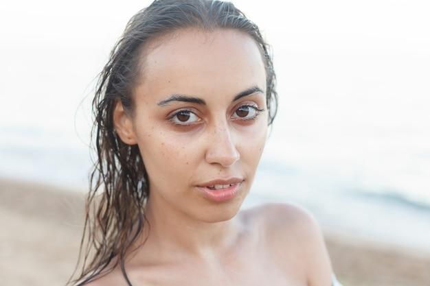 Urlaub, resort, tourismuskonzept - schöne, attraktive frau im schwarzen bikini. junges und sportliches mädchen, das im sommer an einem strand aufwirft.