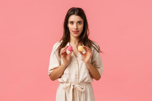 Urlaub, schönheit und süßigkeiten konzept. charmante kaukasische frau im kleid, hält macarons und leckt lippen vom verlangen versuchen dessert, besuchen lieblings süßwarenladen, stehende rosa wand