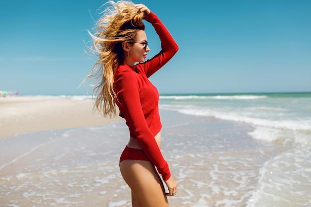 Urlaub und reisekonzept. wunderblonde frau, die auf den ozean schaut. trägt sexy roten bikini. leerer strand. tropische insel. perfekte figur.