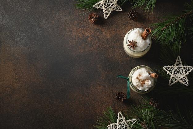 Urlaub weihnachten alkohol eierlikör mit geschlagenen eiern, milch, zimt und geriebener muskatnuss auf braunem hintergrund. platz kopieren. traditionelles weihnachtsfeiertagsgetränk.