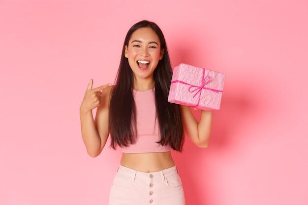 Urlaubs-, feier- und lifestyle-konzept. schönes glückliches asiatisches mädchen, das auf sich selbst zeigt, sein ihr geburtstag, erhalten geschenk, eingewickelt in rosa papier, das breit über wand lächelt.