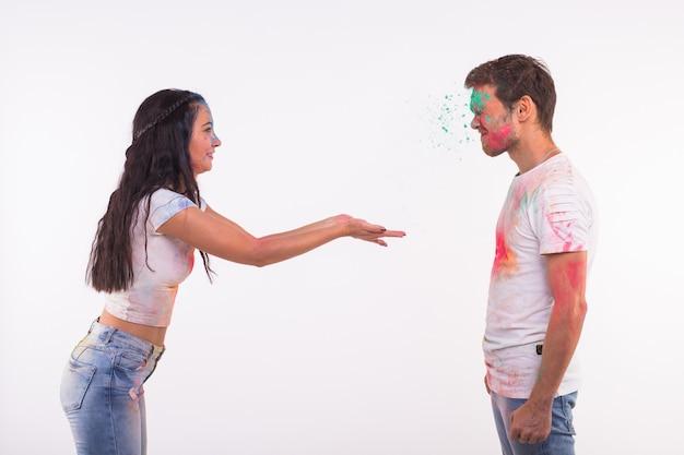 Urlaubs-, ferien- und personenkonzept - glückliches paar, das spaß hat, der in farbe auf weißer wand bedeckt wird