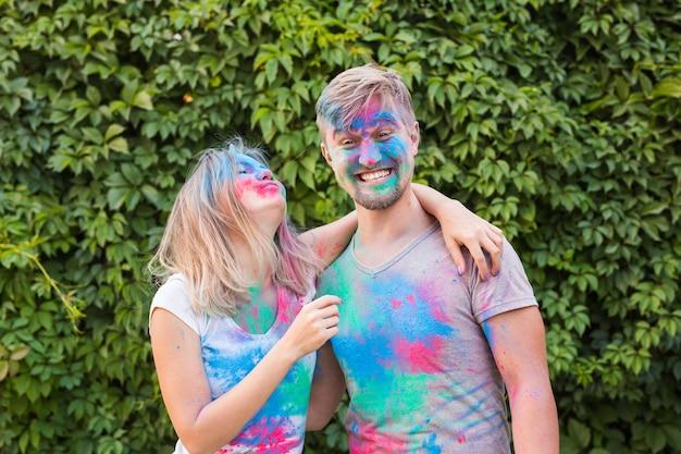 Urlaubs-, ferien- und personenkonzept - glückliches paar, das spaß hat, der in farbe bedeckt wird