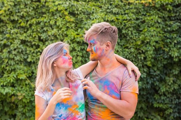 Urlaubs-, ferien- und personenkonzept - glückliches paar, das spaß in farbe bedeckt hat