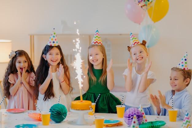 Urlaubs- und festveranstaltungskonzept. glückliche fünf kleine kinder klatschen in die hände, schauen auf funkeln vom kuchen, feiern freundegeburtstag