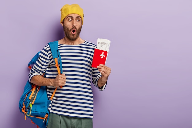Urlaubs- und reisekonzept. überrascht posiert unrasierter typ mit rucksack auf den schultern