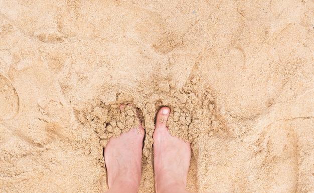 Urlaubsferien. frauenfußnahaufnahme des mädchens, das am strand im sonnigen sommertag entspannt.