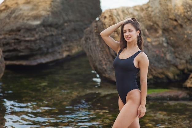 Urlaubskonzept am strand. sommerruhe. junge sexy frau in einem badeanzug an einem wilden strand mit steinen