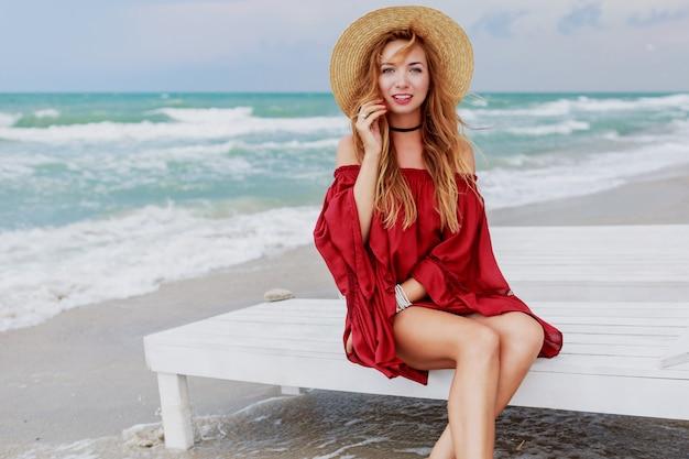 Urlaubskonzept. hübsche hübsche frau des ingwers im stilvollen strohhut und im roten strandkleid, die nahe dem ozean sitzen. wochenenden genießen.