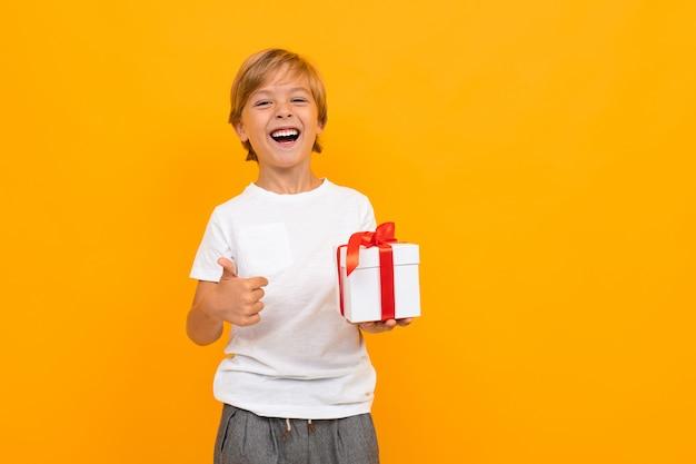 Urlaubskonzept. kleiner junge mit geschenkbox auf leuchtendem gelb