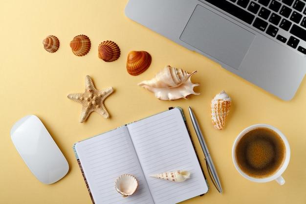 Urlaubskonzept mit laptop und tasse kaffee und muscheln