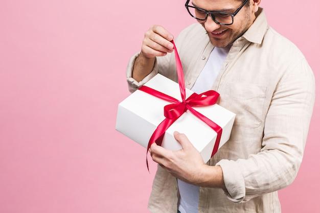 Urlaubskonzept. porträt eines jungen mannes, der geschenkbox lokalisiert über rosa wand öffnet.