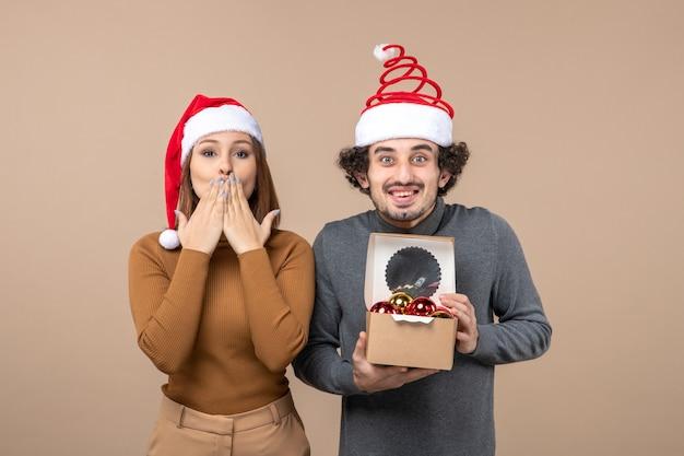 Urlaubsstimmung mit aufgeregtem coolem paar, das rotes weihnachtsmannhutmädchen trägt, das kuss auf grau sendet