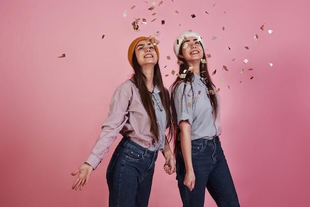 Urlaubsstimmung. neujahrskonzeption. zwei zwillinge spielen und werfen goldenes konfetti in die luft