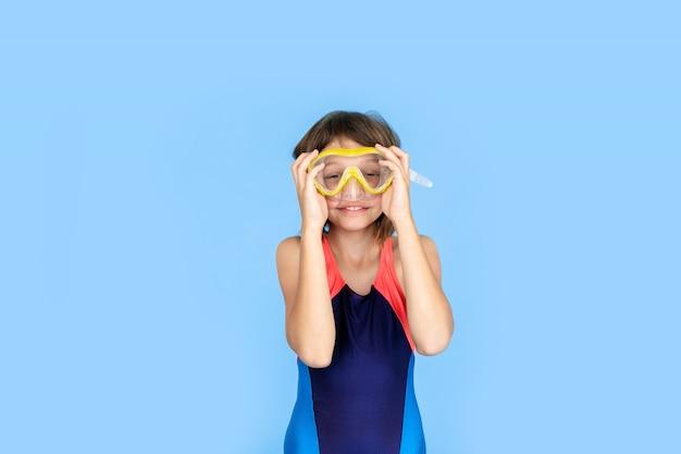 Urlaubsthema: kindermädchen mit schnorchel- oder tauchausrüstung an einer blauen wand. abenteuer- und ruhekonzept