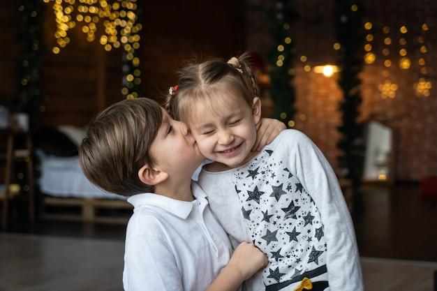 Urlaubsvorbereitungen. zwei kinderkinder genießen viele weihnachtsgeschenke im haus. kalter winter, schneewetter.