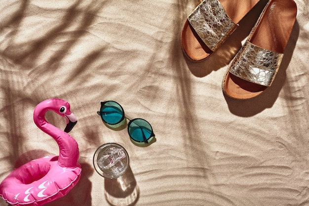 Urlaubszubehör für reisende ist auf einem weißen strandsand ausgelegt, der flach von oben liegt