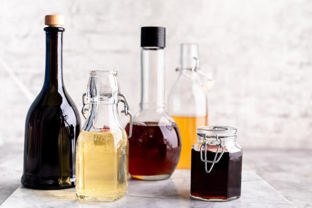 Ursprüngliche glasflaschen mit verschiedenem essig auf einem marmortisch gegen einen tisch einer weißen backsteinmauer. speicherplatz kopieren. horizontal.