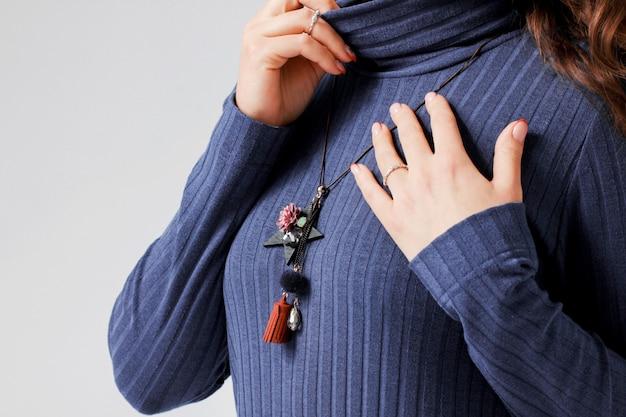Ursprüngliche halskette auf junger frau im blauen beiläufigen kleid