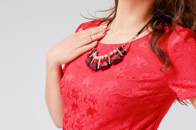 Ursprüngliche halskette auf junger frau im roten eleganten kleid