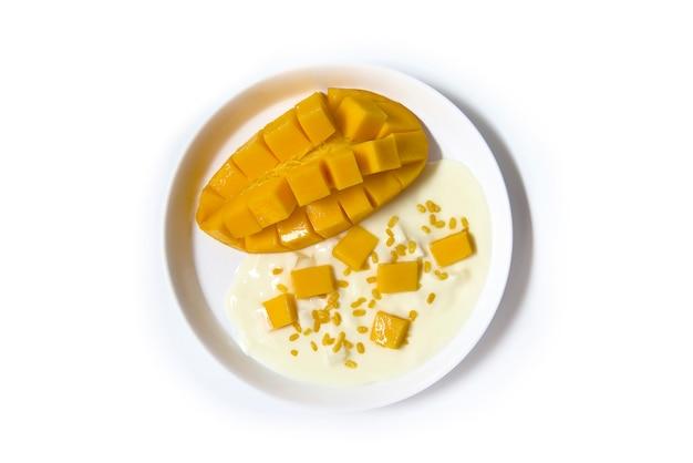 Ursprüngliches aroma des griechischen joghurts mit frischer thailändischer mango des ausschnitts auf der weißen platte