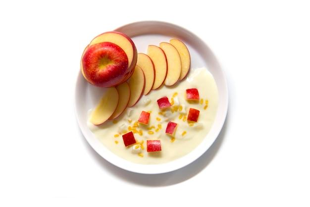 Ursprüngliches aroma des griechischen joghurts mit rotem apfel der frischen scheibe auf der weißen platte