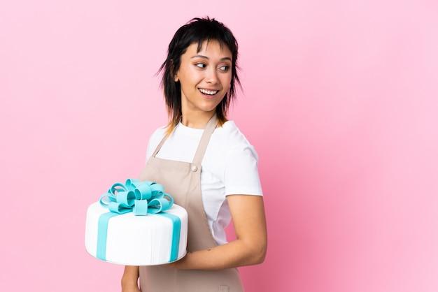 Uruguayischer konditor, der einen großen kuchen über rosa wand lachend hält