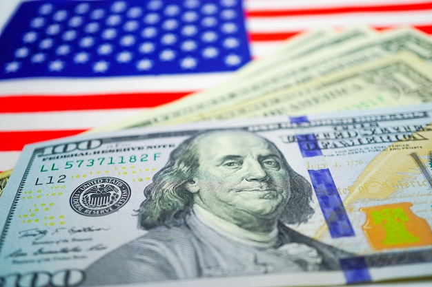 Us-dollar-banknoten auf us-flagge. geschäfts- und finanzkonzept.