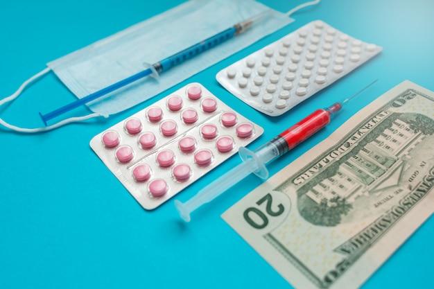 Us-dollar-banknoten. medizinische maske, impfstoffspritze und rosa pillen, pillenblase. wirtschaftskrise. gesundheitsausgaben. ausbruch des coronavirus.