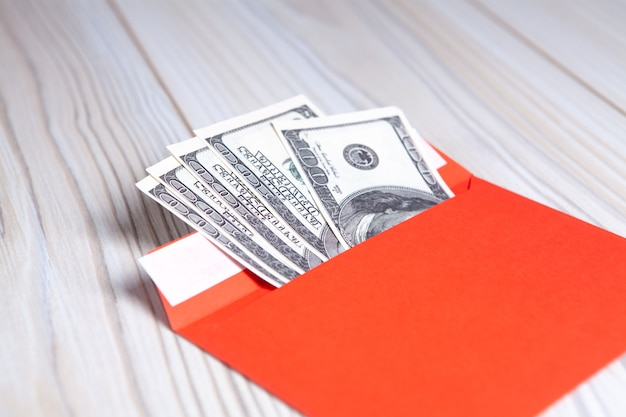 Us-dollar in einem umschlag auf einem holztisch. konzept für einkommen, boni oder bestechung.