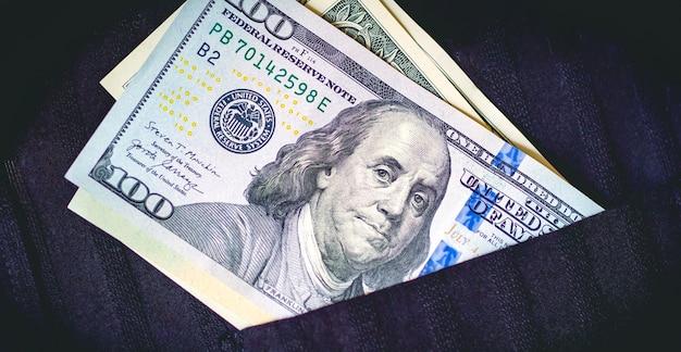 Us-dollar-scheine in einer schwarzen hemdtasche