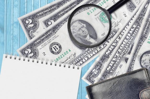 Us-dollar-scheine und lupe mit schwarzer geldbörse und notizblock