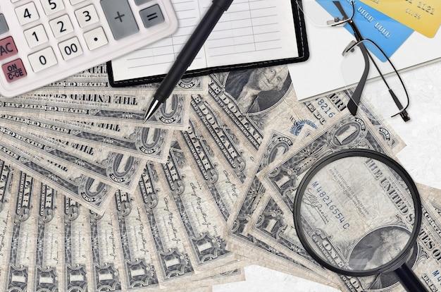 Us-dollar-scheine und taschenrechner mit brille und stift