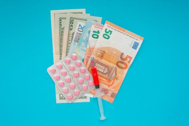 Us-dollar und euro-banknoten. medizinische maske, impfstoffspritze und rosa pillen, pillenblase. wirtschaftskrise. gesundheitsausgaben. ausbruch des coronavirus.