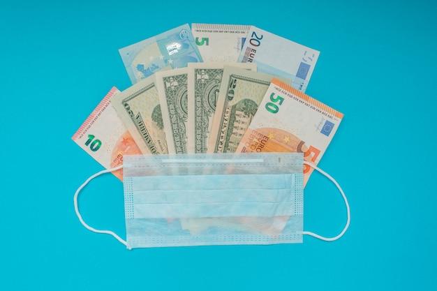 Us-dollar und euro-banknoten und medizinische maske. wirtschaftskrise. gesundheitsausgaben. ausbruch des coronavirus.