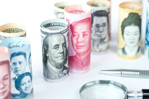 Us-dollar und yuan banknote unter internationalen banknoten. es ist ein symbol für die zolltarifliche handelskriegskrise zwischen den vereinigten staaten von amerika und china, dem größten wirtschaftsland der welt.