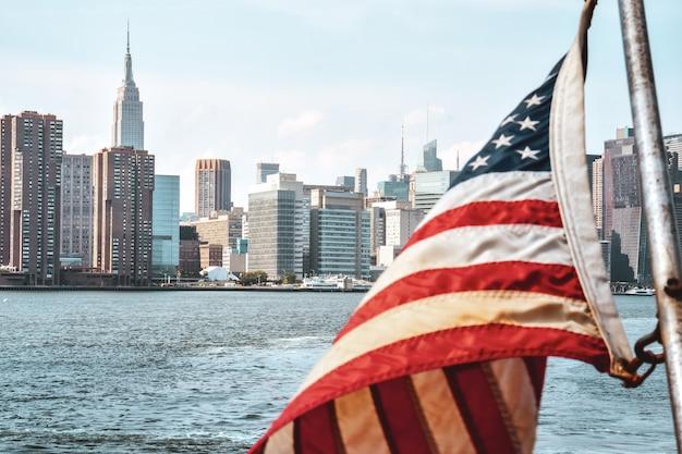 Us-flagge im vordergrund und bürogebäude und wohnungen auf der skyline bei sonnenuntergang. immobilien- und reisekonzept. manhattan, new york city, usa.