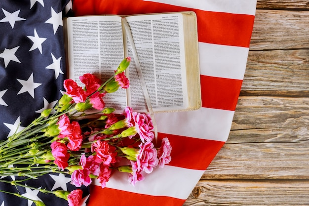 Us-flagge mit dem beten über einer offenen lesenden heiligen bibel auf einer nahaufnahme von amerika beten