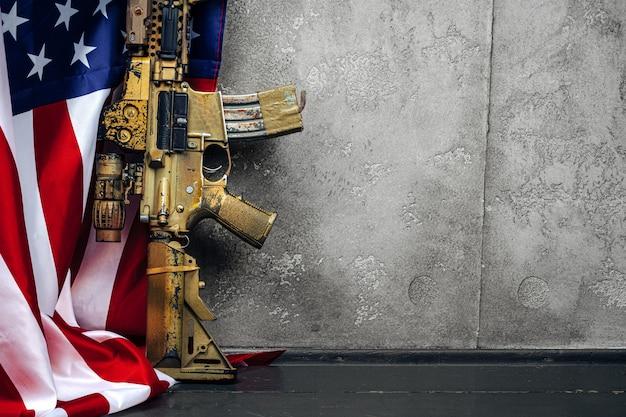 Us-schlachtflagge und sturmgewehr in der nähe der mauer. nahansicht.