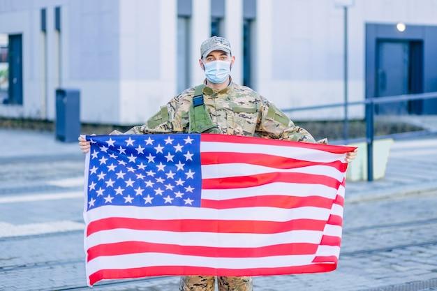 Us-soldat, der die amerikanische flagge hält und eine schutzmaske trägt