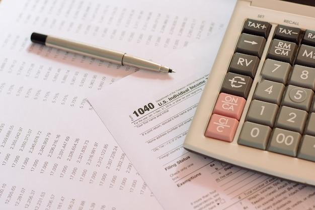 Us-steuerformular mit selektivem fokus des stiftes und des taschenrechners / besteuerungskonzept