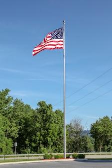 Usa-flagge auf pfosten im blauen himmel bei usa