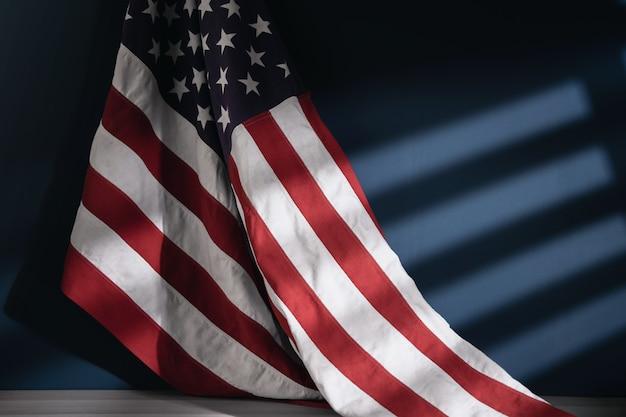 Usa-flagge, die an der wand hängt. amerikanisches symbol. 4. juli oder memorial day der vereinigten staaten. morgensonnenlicht durch das fenster