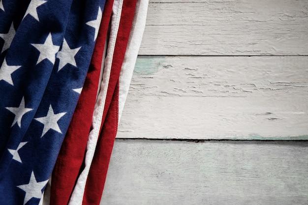 Usa-flagge, die auf verwitterten weinlese-hölzernen hintergrund liegt. amerikanisches symbol. 4. juli oder gedenktag