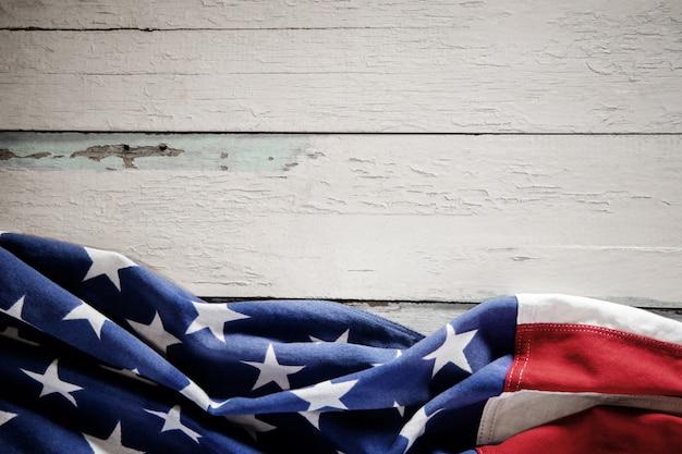 Usa-flagge, die auf verwitterten weinlese-hölzernen hintergrund liegt. amerikanisches symbol. 4. juli oder memorial day der vereinigten staaten